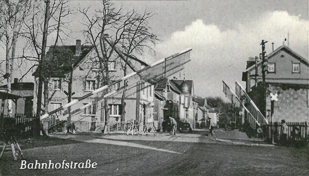 Der Bahnübergang auf einer Postkarte von 1958. Zu sehen ist die Bahnhofstraße in Fahrtrichtung Hausen.