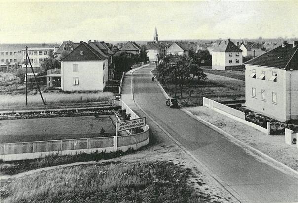 Die Seligenstädter Straße in Hausen 1939. Der hier gezeigte Ortseingang lag damals in Höhe der heutigen Sparkassenfiliale. Man beachte die unbefestigten und zum Teil nicht vorhandenen Gehwege.