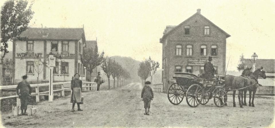 """Noch nahezu unverbaut präsentierte sich um 1900 der Blick von Obertshausen über den Bahnübergang in Richtung Hausen. Links ist die Wirtschaft """"Zum Forsthaus"""", rechts die Gaststätte """"Zum Bahnhof"""" zu sehen."""